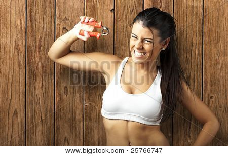 portrait of sporty young woman doing exercise against a wooden wall