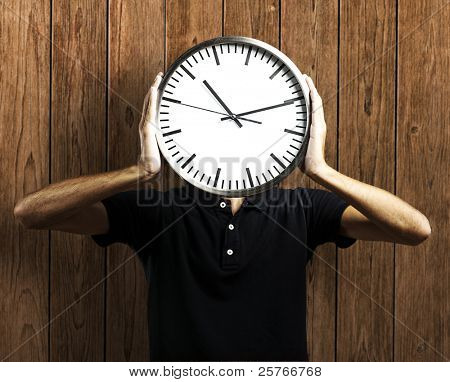 Young man holding clock against a wooden wall