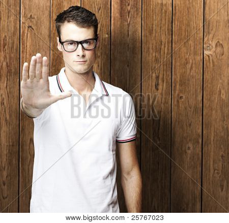 portrait of young man doing stop symbol against a wooden wall