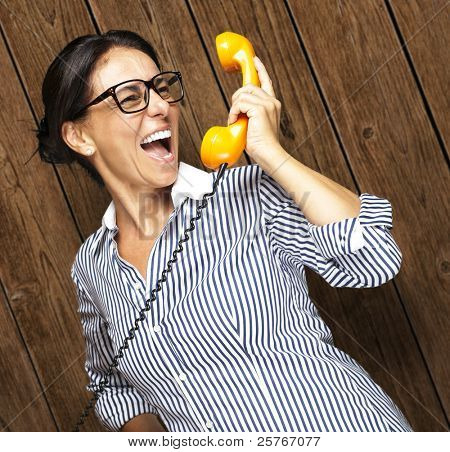 portrait of middle aged woman talking on vintage telephone against a wooden wall