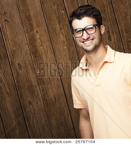 portrait of young man smiling with glasses against a wooden wall