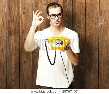 retrato de jovem homem segurando o telefone vintage contra uma parede de madeira