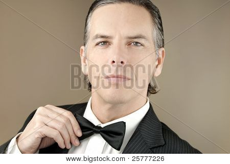 Confident Gentleman In Tux Adjusts Bowtie