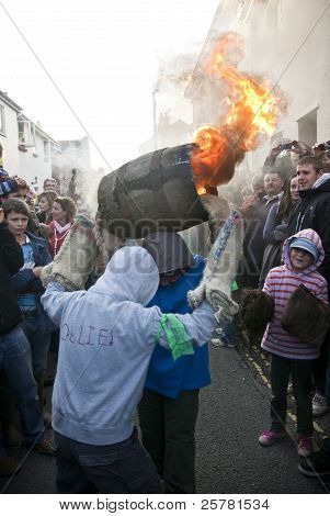 Two Young Barrel Rollers Exchange A Burning Barrel At The 2011 Tar Barrels Of Ottery Carnival On San