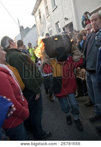 A Colorful Young Barrel Roller Runs Through The Streets Of Ottery St Mary With A Burning Barrel At T