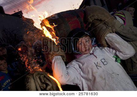 Niña corriendo con un barril de alquitrán ardiente en el 2011 barriles de alquitrán en carnaval Ottery.