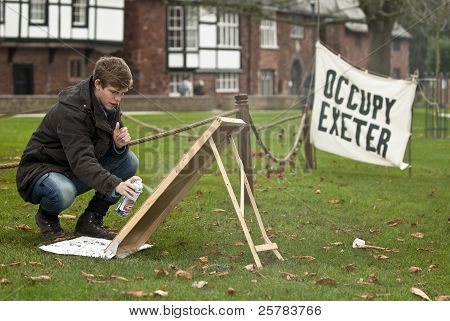 Occupy Exeter activist prepares a sign at the Occupy Exeter Camp