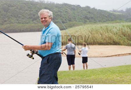 happy senior man fishing with grandsons by the lake