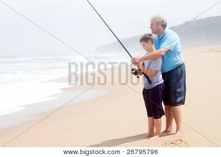 grandfather teaching teen grandson fishing on beach