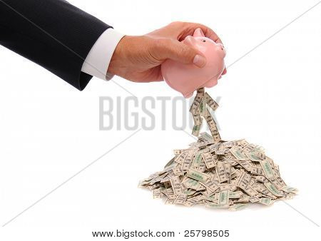 Businessmans hand holding a pink piggy bank over a pile of hundred dollar bills with some bills spilling out. Bills are mini replicas of US One Hundred dollar bills. Over white with reflection.