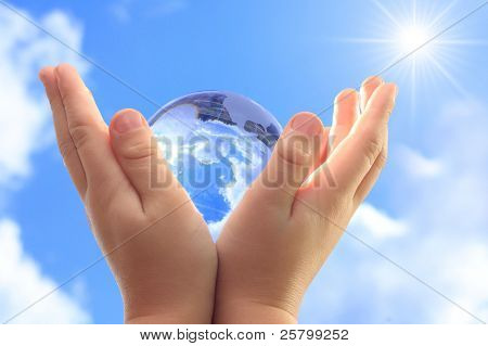 Globe on child hand against blue sky.