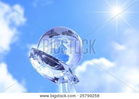 Globe on cristal hand against blue sky.
