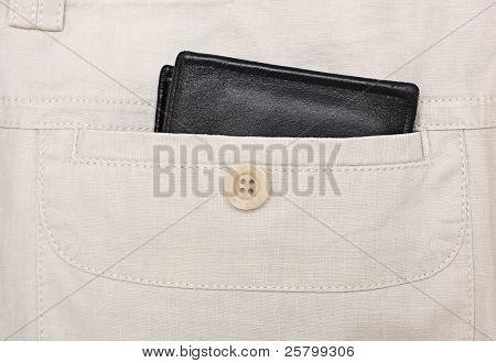 Black wallet in a back pocket in linen trousers.