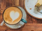 Cup Of Cappuccino With Latte Art And A Cheesecake Near It On A Brown Wooden Background. Stylish Foam poster