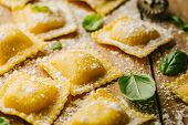 Tasty Raw Ravioli With Flour And Basil On Wooden Background. Process Of Making Italian Ravioli. Clos poster