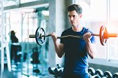 Fit Caucasian Handsome Young Man And Big Muscle In Sportswear. Young Man Holding Dumbbell During An  poster