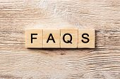Faqs Word Written On Wood Block. Faqs Text On Table, Concept. poster