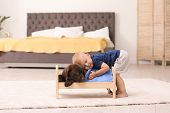 Little Boy Playing With Adorable Chocolate Labrador Retriever At Home poster