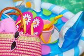 picture of floaties  - Pool toys and accessories on deck next to pretty pool water - JPG