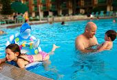 image of floaties  - Father having fun with children in big swimming pool - JPG