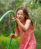 picture of hulahoop  - Young girl playing with hula hoop outside - JPG