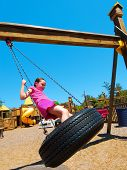 stock photo of swingset  - Young girl having fun on tire swing at pretty park - JPG
