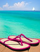stock photo of convection  - Pink flip flop sandals on dock overlooking gorgeous ocean with sailboat in distance - JPG