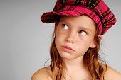 stock photo of newsboy  - Freckle faced young girl looking up wearing pink plaid cap - JPG