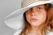 picture of spoiled brat  - Young freckle faced girl with serious look wearing big hat - JPG