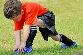 pic of hamstring  - young boy on field stretching before soccer game - JPG