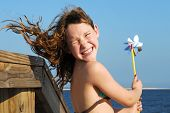 stock photo of hair blowing  - Young girl at windy beach having fun with pinwheel - JPG