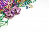 stock photo of carnivale  - Mardi gras mask and beads in pile - JPG