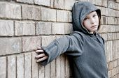 stock photo of delinquency  - girl in hooded jacket outside - JPG