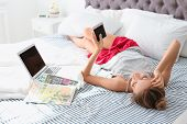 Beautiful Young Woman Using Smartphone In Bed At Home. Lazy Morning poster
