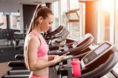 Slim Beautiful Woman With A Ponytale Standing On The Treadmill In The Gym Holding A Phone Wearing Ea poster