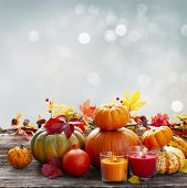 Fall Harvest Of Pumpkins With Leaves And Candles On Wooden Table, Copy Space On Fall Gray Sky Backgr poster