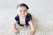 Cute Adorable Baby Girl In Blue Clothes And Headband. Little Child Looking At The Camera And Crawlin poster