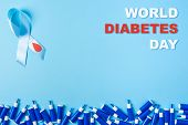 Inscription World Diabetes Day Blue Ribbon Awareness With Red Blood Drop And Line Of Lancets On A Bl poster