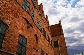 Historic Brick Building With Cloudy Sky poster
