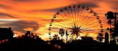 stock photo of carnival ride  - Panorama of a carnival silhouetted against the evening skyline at dusk - JPG