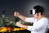Young Asian Man In Casual White Outfit Holding Or Wearing Vr Glasses Goggles Playing Car Racing Vide poster
