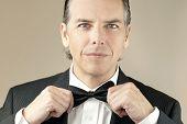 Confident Gentleman In Tux Adjusts Bowtie With Both Hands poster