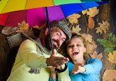 Hipster With Beard And Cheerful Girl Expect Rainy Weather Hold Colorful Umbrella. Couple In Love Lay poster