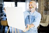 Aged artist with painted face standing in front of his easel and painting in studio of arts poster