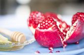 A Beautiful View Of An Open Ripe Pomegranate Fruit With Pomegranate Seeds Seen. Apple Slices Dipped  poster