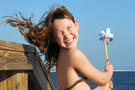picture of hair blowing  - Young girl at windy beach having fun with pinwheel - JPG