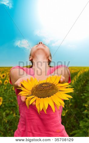 girl with a sunflower against the sky