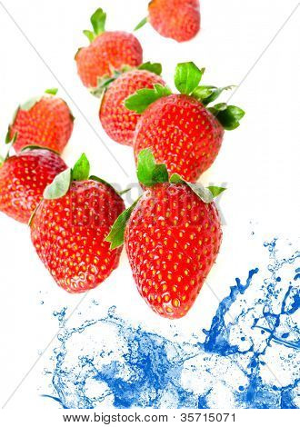 Strawberry falling in juice. Isolation.