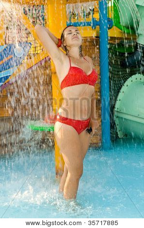 girl in a bathing suit under a shower