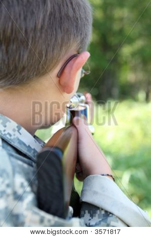 Young Child Holding Play Rifle And Aiming It Into The Woods